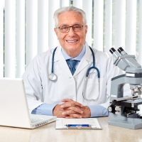 Elderly doctor man in clinic. Health care background.